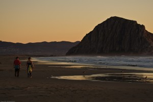 Couple walks on the Morro Strand State Park beach at sunset
